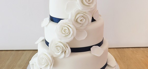 Wedding Cake with With Roses and Navy Ribbon
