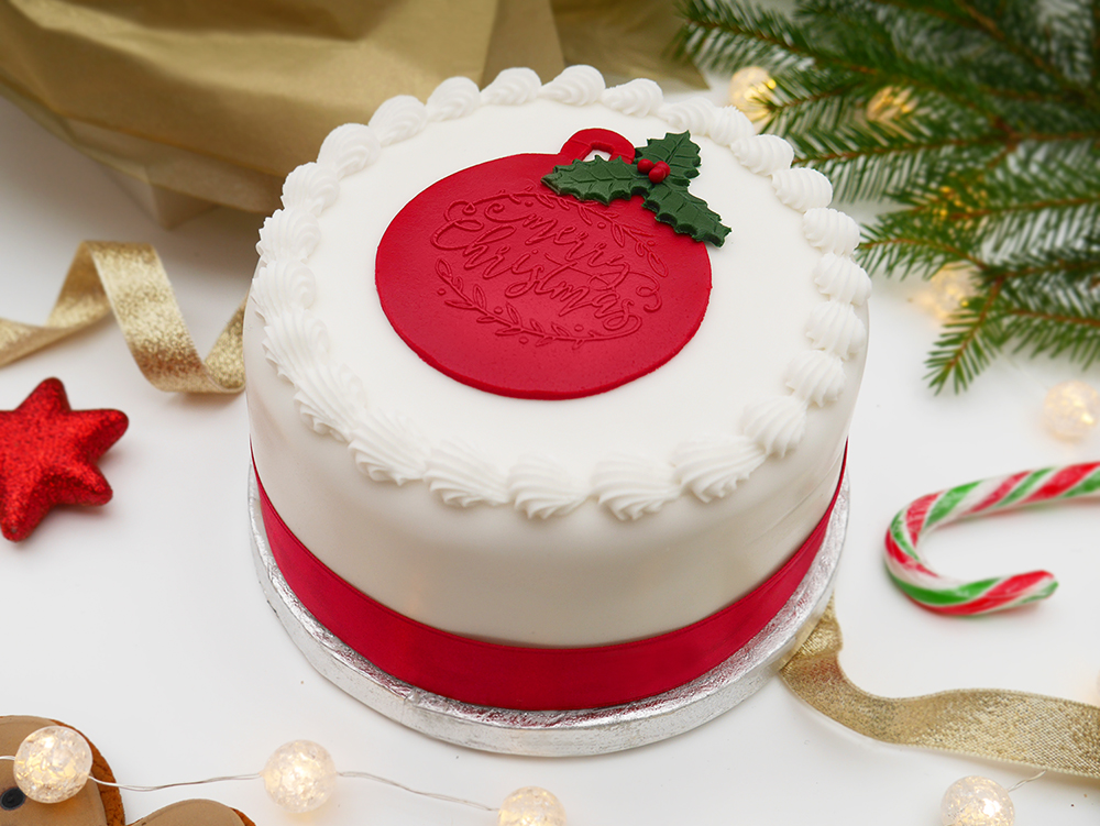 A traditional Christmas cake with a red bauble design and red ribbon.