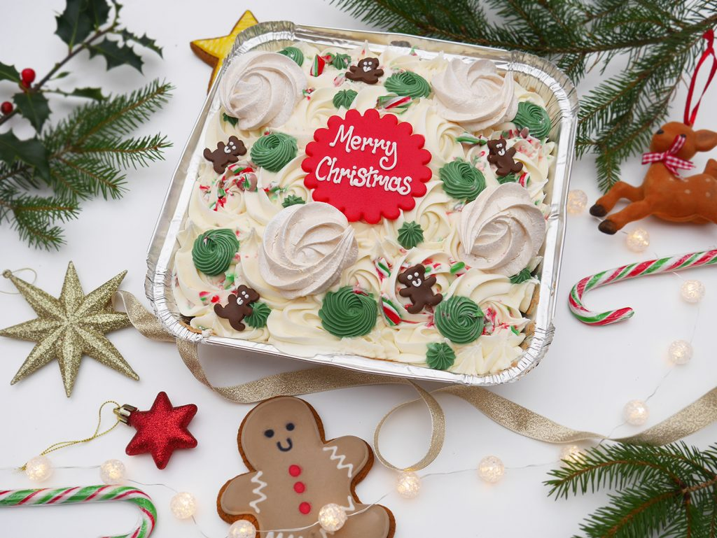 A Christmas Traybake cake with swirly buttercream icing and festive decoration